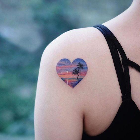 Chica con tatauje en forma de corazón con dibujo del mar en un atardecer en el interior