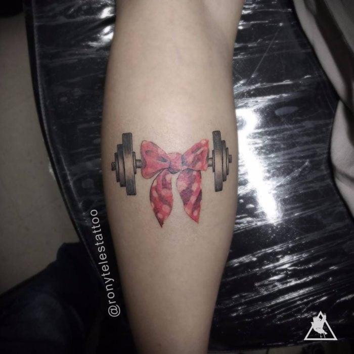 Chica con un tatuaje en el brazo de unas pezas