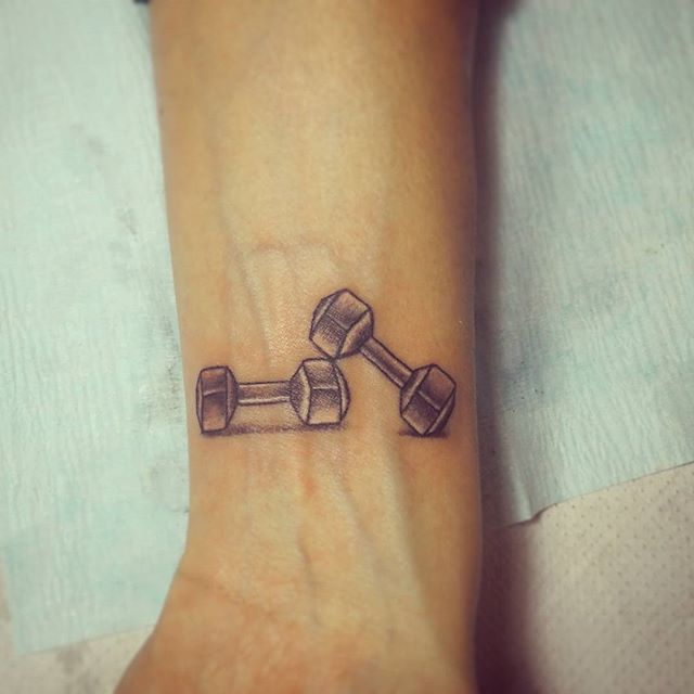 Girl with a tattoo on the arm of some dumbbells