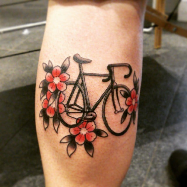 Girl with a tattoo on the arm of a bicycle with flowers