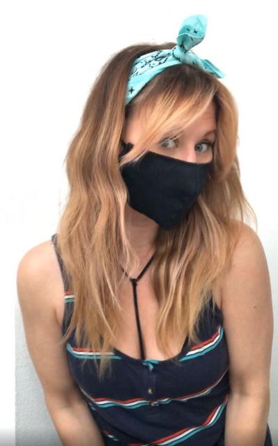 Chica usando una mascarilla sujetada con una bandana