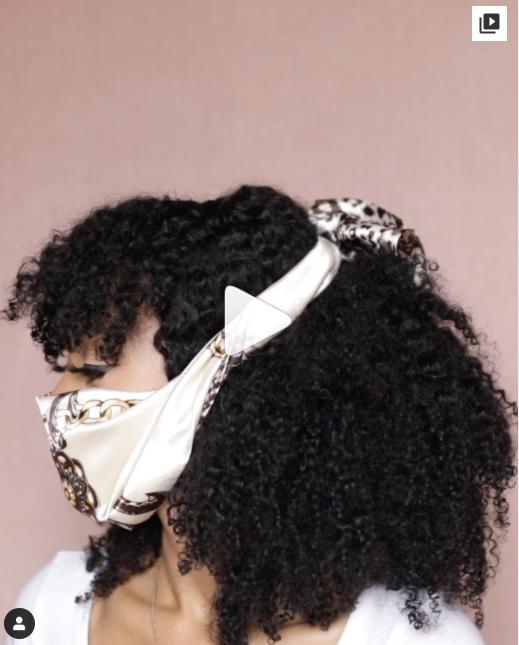 Chica de cabello chino mostrando cómo sujetar una mascarilla