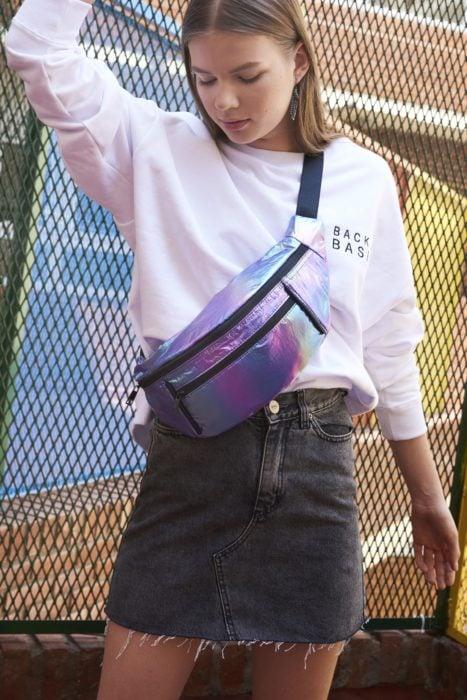 Chica usando una riñonera en tono tornasol