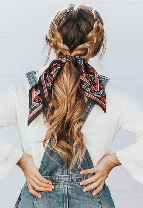 2-braid hairstyle gathered in a low ponytail adorned with a scarf