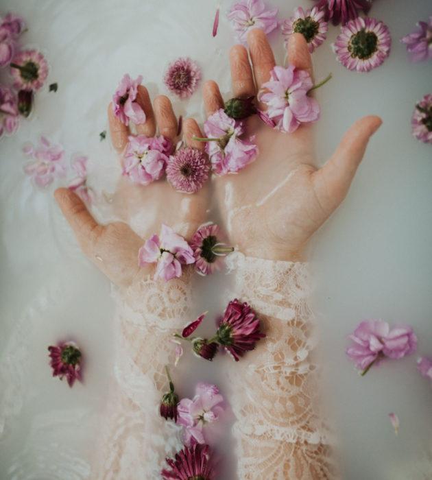 Milk bath; fotografía de manos de mujer en el agua con leche y flores mroadas