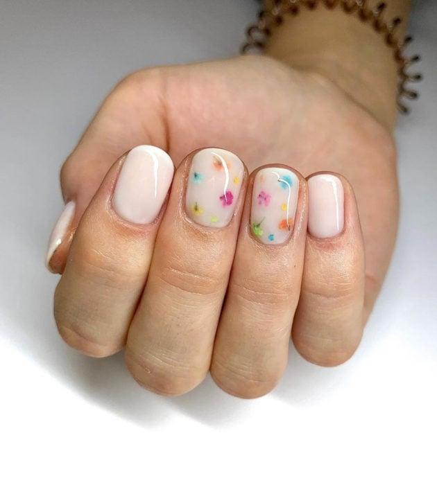 Diseños de manicura milk bath; uñas cortas color blanco con clores pequeñas azules, amarillas, anaranjadas, verdes y rosas