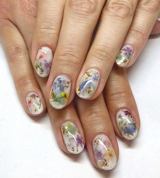 Diseños de manicura milk bath; uñas cortas color blanco con flores azules, amarillas y moradas