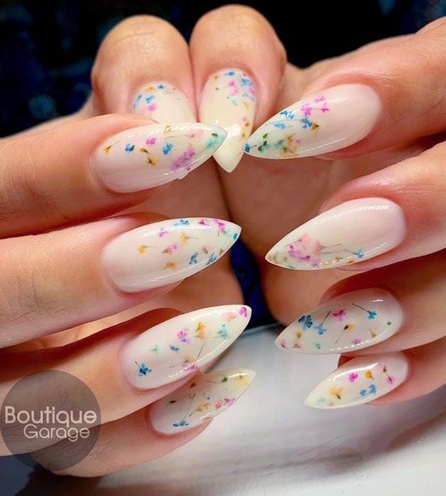 Diseños de manicura milk bath; uñas largas stiletto color blanco con flores rosas, amarillas y azules