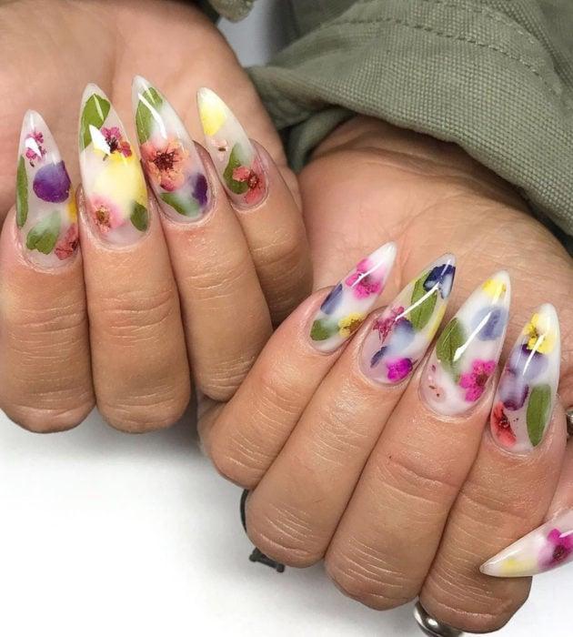 Diseños de manicura milk bath; uñas largas stiletto color blanco con flores moradas, rosas y azules