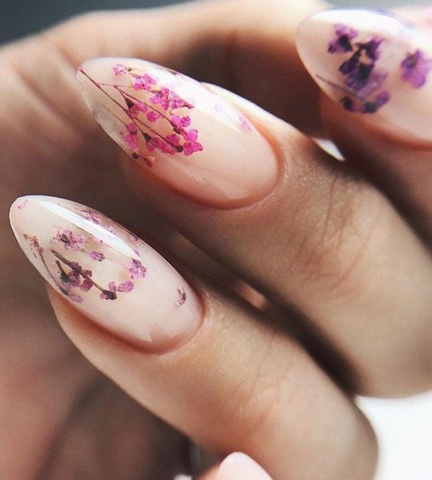 Diseños de manicura milk bath; uñas almendras color rosa pálido con flores pequeñas