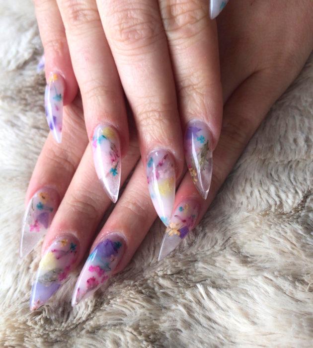 Diseños de manicura milk bath; uñas largas stiletto color lilas con flores rosas, amarillas y azules