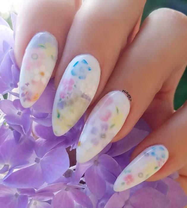 Diseños de manicura milk bath; uñas stiletto largas blancas con flores moradas, azules, amarillas y rosas