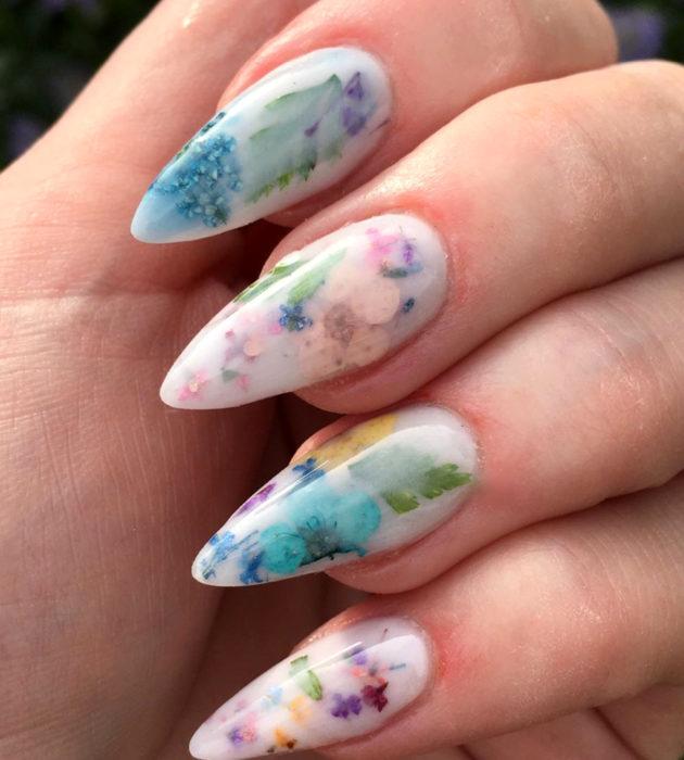 Diseños de manicura milk bath; uñas largas stiletto, blancas con flores azules, rosas, amarillas y moradas