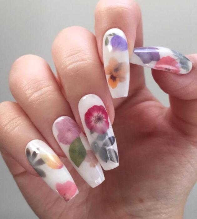 Diseños de manicura milk bath; uñas largas cuadradas,blancas con flores rosas, rojas, anaranjadas y moradas con hojas verdes