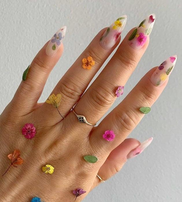 Diseños de manicura milk bath; uñas largas stiletto, blancas con flores rosas, amarillas, azules y moradas, hojas verdes