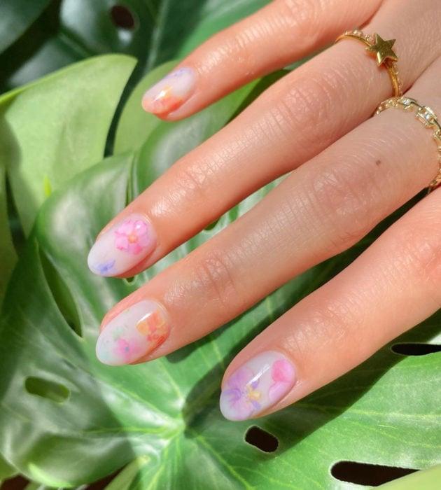 Diseños de manicura milk bath; uñas cortas redondas, blancas con flores rosas, moradas y anaranjadas