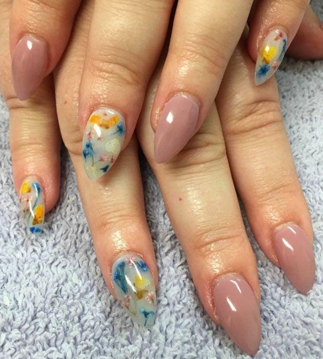 Diseños de manicura milk bath; uñas en forma de almendra, color nude y blanco con flores rosas, azules y amarillas