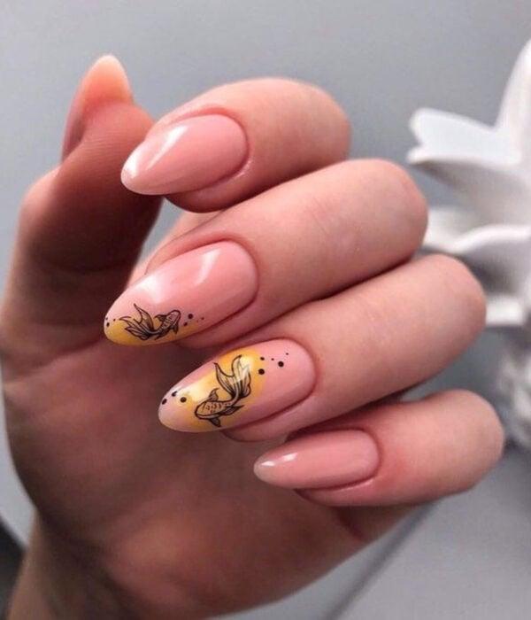 Diseño de manicure sencillos, femeninos y naturales; uñas largas en forma de almendra pintadas con esmalte nude y amarillo con dibujo de pez beta