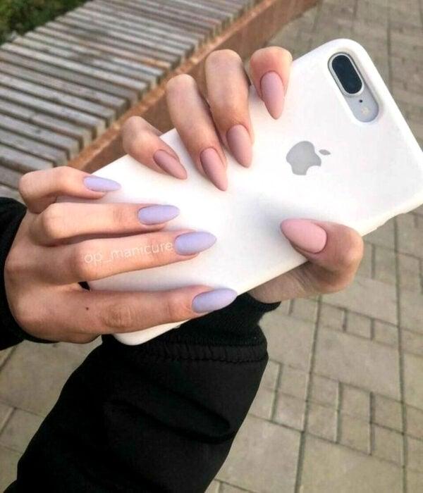 Diseño de manicure sencillos, femeninos y naturales; uñas largas en forma de almendra pintadas con esmalte rosa palo en una mano y la otra con color lila