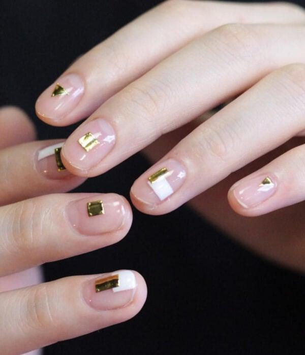 Diseño de manicure sencillos, femeninos y naturales; uñas cortas redondas pintadas con esmalte transparente y cuadrados y triángulos dorados