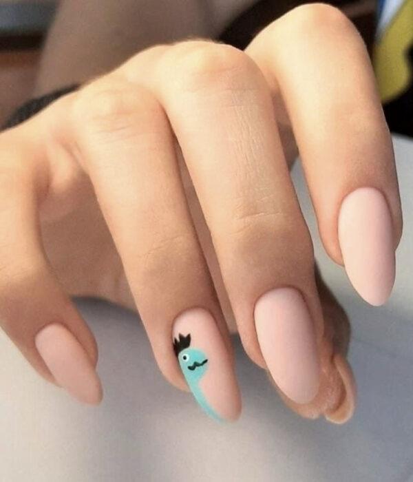 Diseño de manicure sencillos, femeninos y naturales; uñas largas en forma de almendra pintadas con esmalte nude y dibujo de un dinosaurio azul