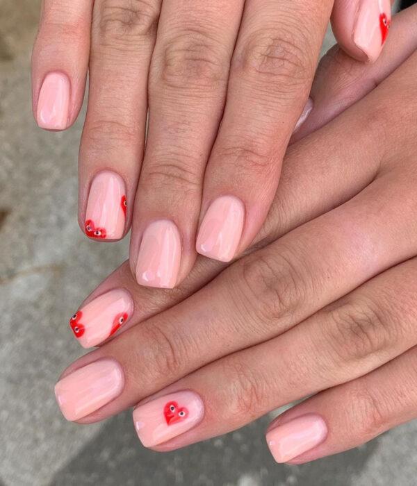 Diseño de manicure sencillos, femeninos y naturales; uñas cortas cuadradas pintadas con esmalte nude rosa y dibujos de corazones rojos con ojos