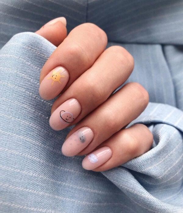 Diseño de manicure sencillos, femeninos y naturales; uñas largas redondas pintadas con esmalte nude y dibujos de Sol, planeta Saturno y nube gris con lluvia y caritas felices