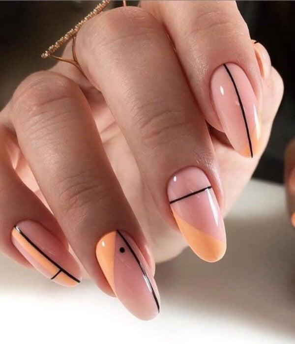 Diseño de manicure sencillos, femeninos y naturales; uñas largas en forma de almendra pintadas con esmalte nude y líneas y puntos negros y anaranjados