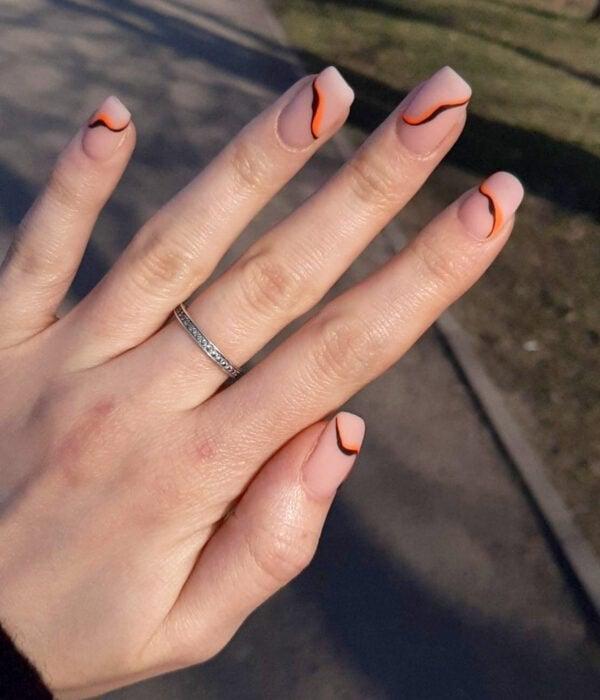Diseño de manicure sencillos, femeninos y naturales; uñas largas cuadradas pintadas con esmalte nude y líneas negras y anaranjadas