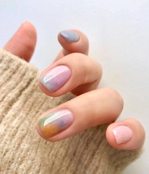 Diseño de manicure sencillos, femeninos y naturales; uñas cortas cuadradas pintadas con esmalte de colores pastel, tosa, morado, verde, azul y amarillo difuminados