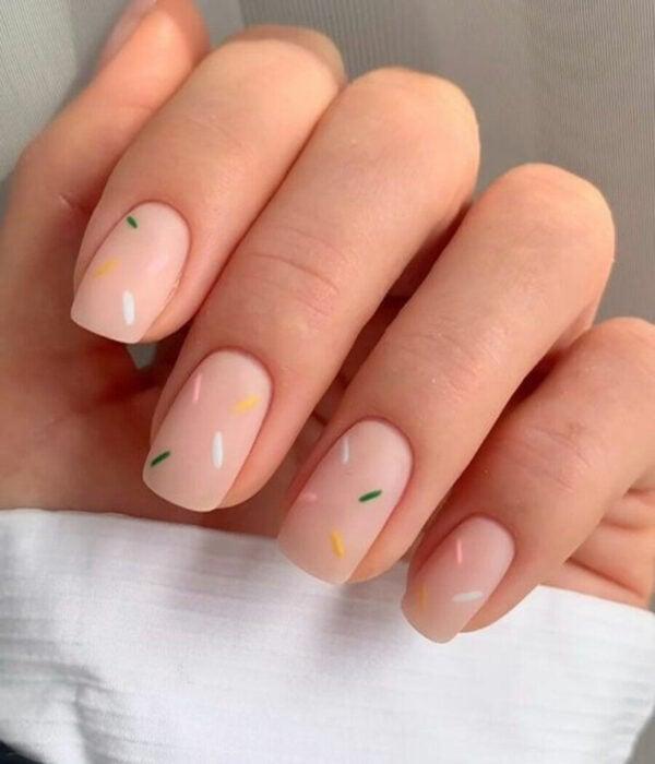 Diseño de manicure sencillos, femeninos y naturales; uñas medianas cuadradas pintadas con esmalte nude y chispas de chocolate verdes, blancas, rosas y amarillas