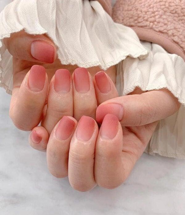 Diseño de manicure sencillos, femeninos y naturales; uñas cortas cuadradas pintadas con esmalte rosa durazno difuminado