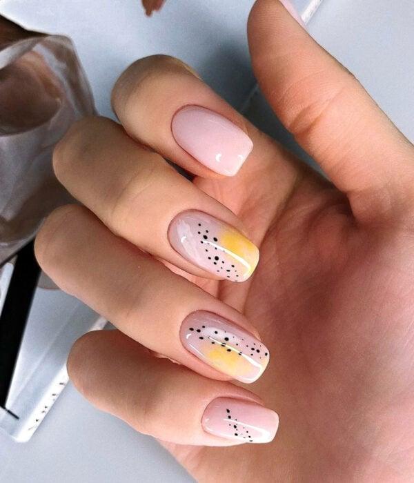 Diseño de manicure sencillos, femeninos y naturales; uñas largas cuadradas pintadas con esmalte nude y dibujos amarillos con puntos negros