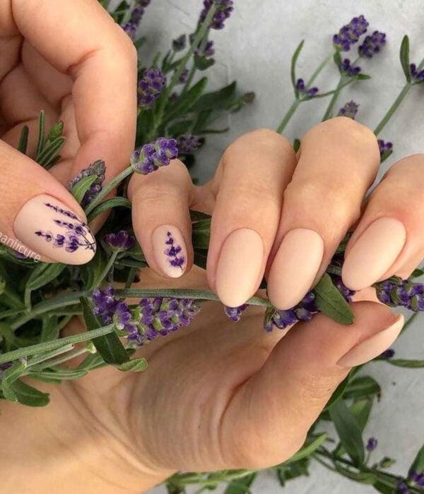 Diseño de manicure sencillos, femeninos y naturales; uñas medianas en forma de almendra pintadas con esmalte nude y dibujo de lavanda