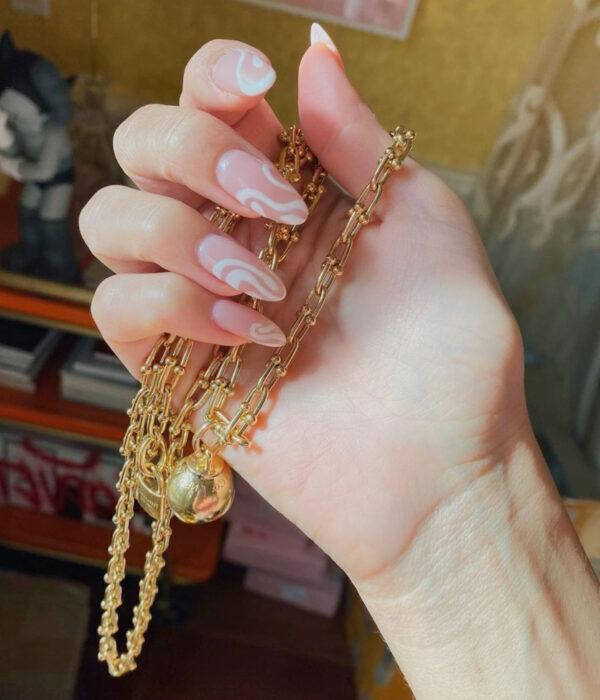 Diseño de manicure sencillos, femeninos y naturales; uñas largas en forma de almendra pintadas con esmalte nude rosa con figuras espirales blancos