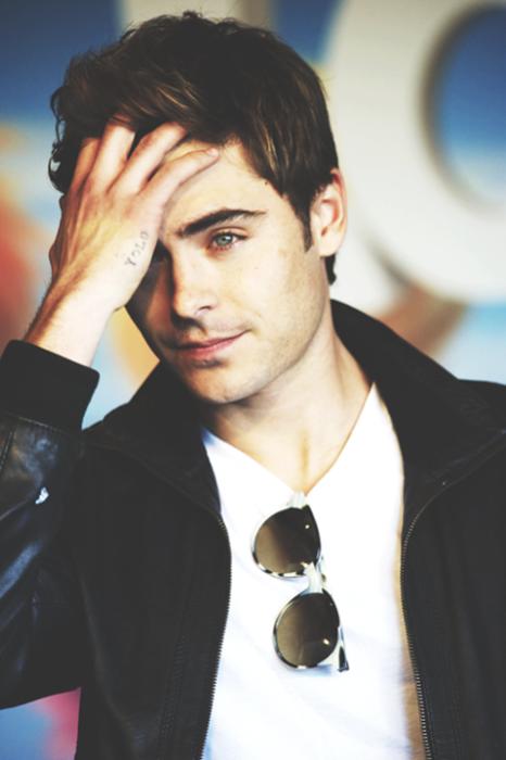 Zac Efron usando playera blanca y con lentes oscuros y chaqueta de cuero