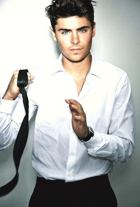 Zac Efron usando camisa de vestir blanca y con la corbata en la mano