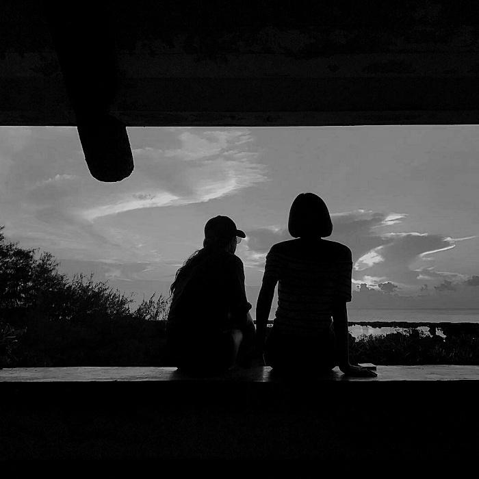 imagen de pareja sentada frente a una ventana