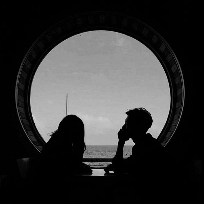 imagen de una pareja frente a una ventana, sentados en una mesa