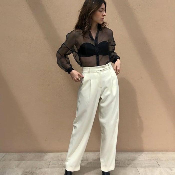 chica de cabello castaño con pantalon de tiro alto color blanco, camisa negra transparente y bustier negro