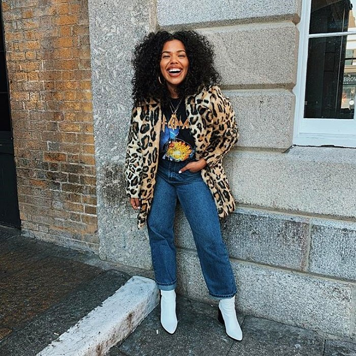 chcia brunette with chinese hair wearing a band t-shirt with animal print jacket, high waisted jeans and white fur boots