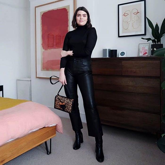 chica de cabello oscuro corto usando un top de cuello alto negro con manga larga y pantalones de tiro alto de cuero, botas y bolso de mano