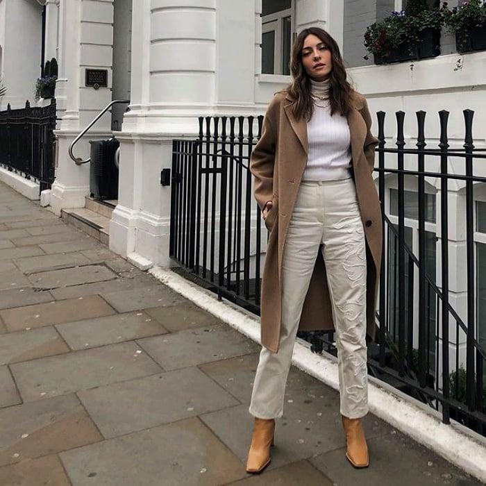 chica de cabello castaño usando un top blanco, abrigo café, pantalones de tiro alto de lino y botas de piel
