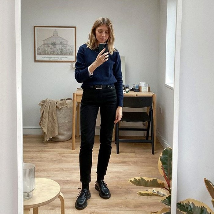 long-haired blonde girl wearing a denim jacket, black high-rise jeans and leather boots