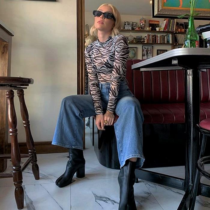 chica rubia con lentes de sol usando un top de animal print, jeans de tiro alto y botas tobi de cuero negro
