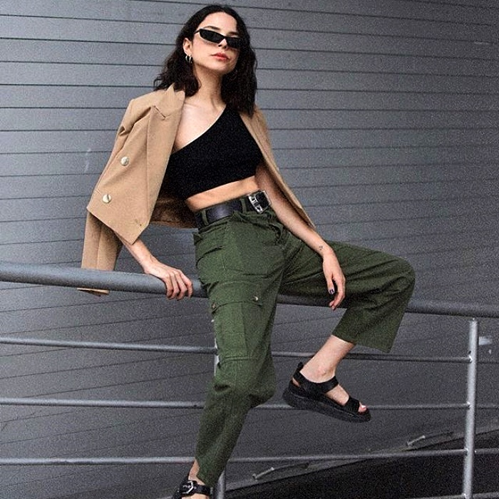 dark-haired girl with sunglasses wearing black top, beige jacket, green cargo pants and black sandals