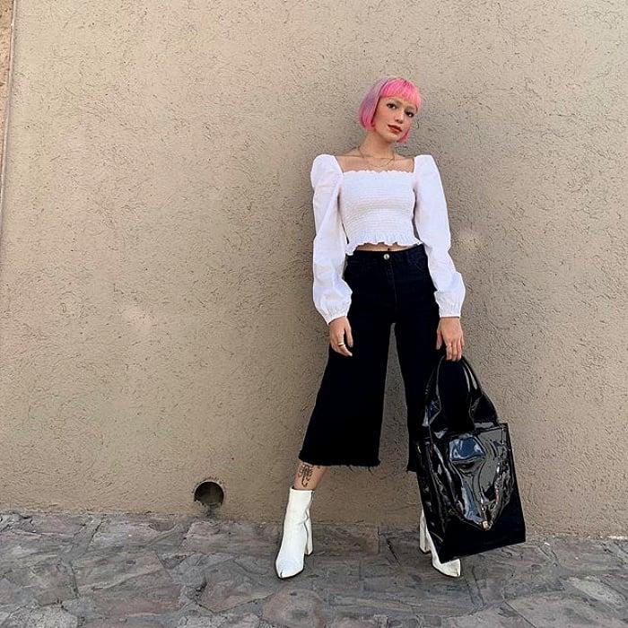 chica de cabello rosa corto usando una blusa blanca de manga larga, pantalones negros tipo culotte y botas blancas