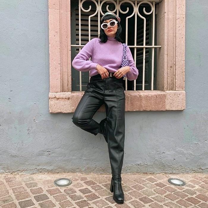 chica de cabello corto negro, usando lentes de sol blancos, top lila tipo suéter, pantalones de tiro alto de cuero y botas negras