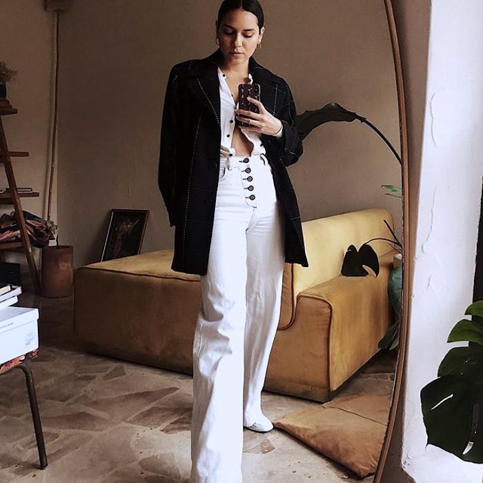 chica morena usando top blanco de botones, saco negro oversized, pantalones de tiro alto blancos con cierre de botones