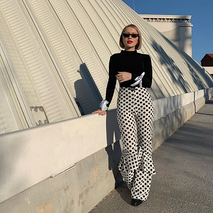 blonde short hair girl with sunglasses wearing a black long sleeve t-shirt, white pants with black polka dots and black shoes
